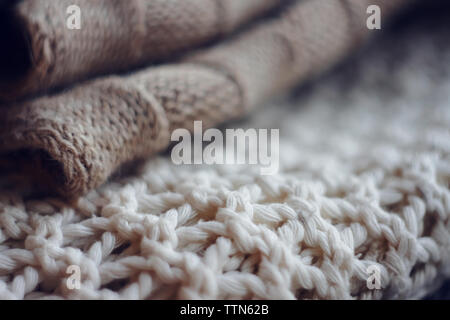 Beige wool sweater and white jumper large knit lie in a pile on top of each other - Stock Photo