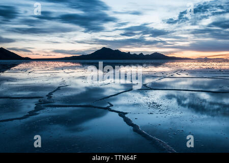 View of the Bonneville Salt Flats against cloudy sky during sunset - Stock Photo