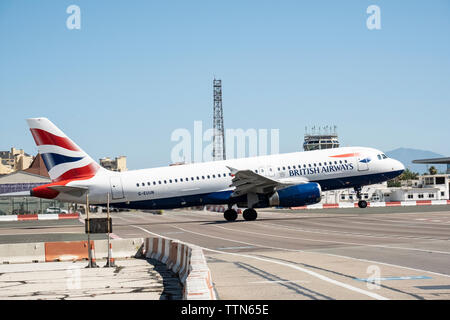 Gibraltar International Airport. British Airways flight to London just lifting off from runway at 150mph+ as it crosses the main road to Spain - Stock Photo
