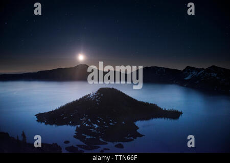 Scenic view of Wizard island in crater lake against sky at night - Stock Photo