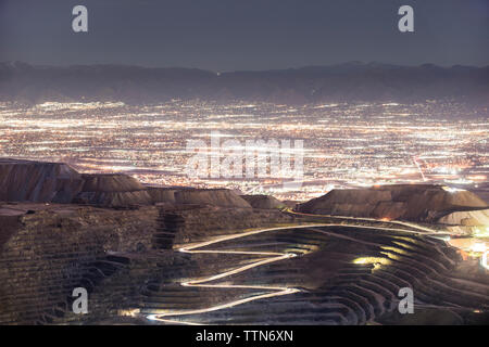 High angle view of Bingham Canyon against illuminated cityscape - Stock Photo