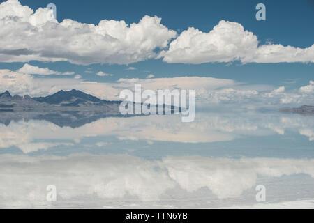 Symmetry view of Bonneville Salt Flats against cloudy sky - Stock Photo