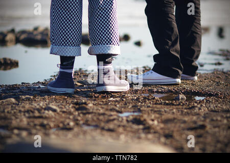 Two people in pants and sneakers are on the rocky beach in Sunny weather - Stock Photo
