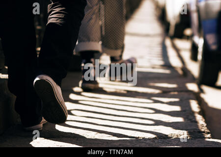 Two guys in pants and sneakers walking on the stone pavement, which falls striped shadow from the fence and there are cars - Stock Photo