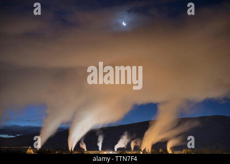 Low angle view of smoke emitting from chimney at dusk - Stock Photo