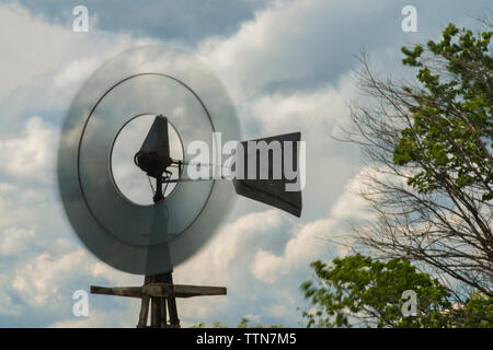 Low angle view of windmill against cloudy sky - Stock Photo
