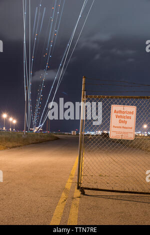 Low angle view of light paintings over road against cloudy sky at night - Stock Photo