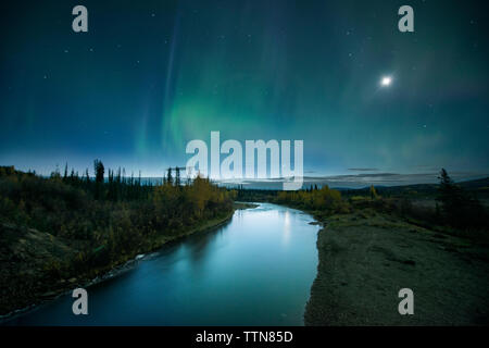 River amidst landscape against sky at night - Stock Photo