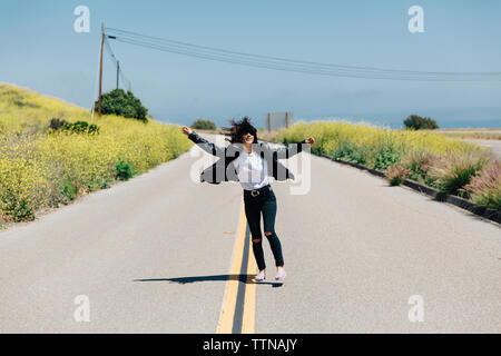 Happy woman with arms outstretched dancing on road amidst plants against blue sky during sunny day - Stock Photo