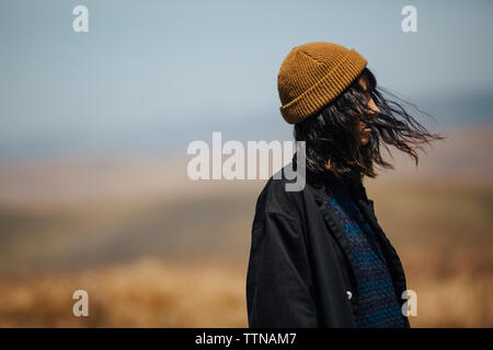 Side view of woman with tousled hair in warm clothing standing against sky during sunny day - Stock Photo