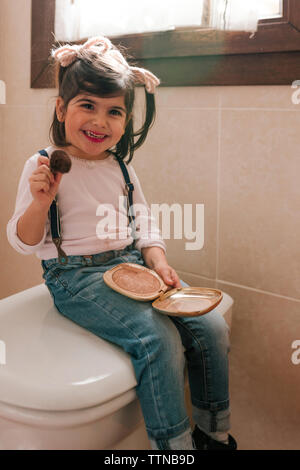Little girl is putting makeup on in the bathroom - Stock Photo