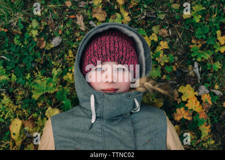 Young woman lying on the grass in warm clothes - Stock Photo