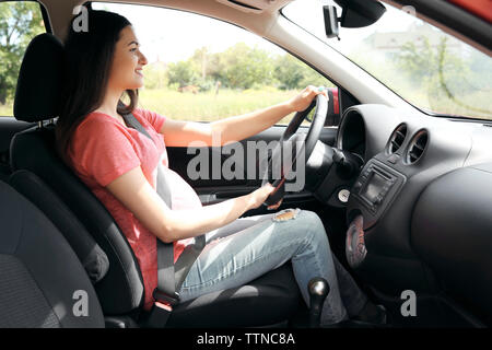 Pregnant woman driving car. Safety drive concept - Stock Photo