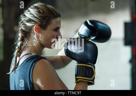 Side view of confident female boxer in gym - Stock Photo