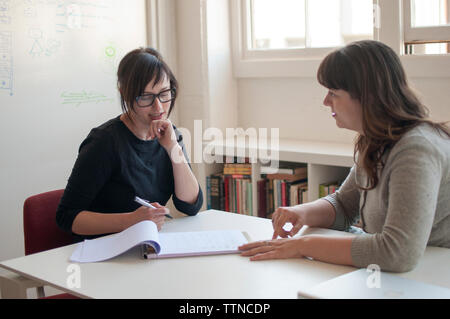 Businesswomen discussing during meeting at desk in new office - Stock Photo