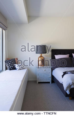 Cushions on window seat in bedroom - Stock Photo