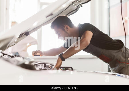 Side view of engineer photographing car engine through mobile phone at auto repair shop - Stock Photo