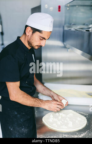 Chef putting cheese on pizza dough in commercial kitchen at pizzeria - Stock Photo