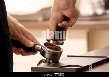 Barista pressing ground coffee with tamper in portafilter - Stock Photo
