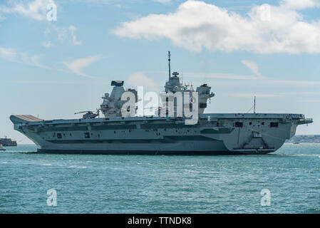 The Royal Navy aircraft carrier HMS Queen Elizabeth leaving Portsmouth Harbour, UK and entering The Solent on 17/6/19 to continue aircraft trials. - Stock Photo