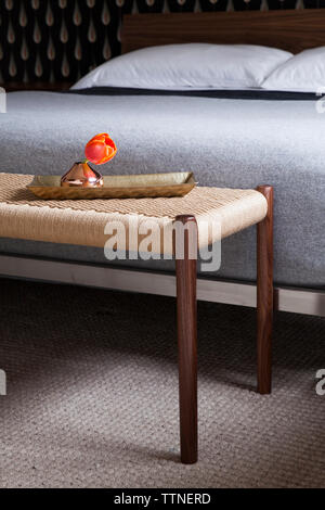 Rose flower in vase on footrest in bedroom at home - Stock Photo