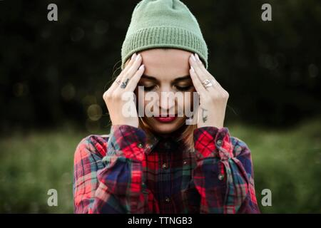 Young woman with head in hands standing on field - Stock Photo