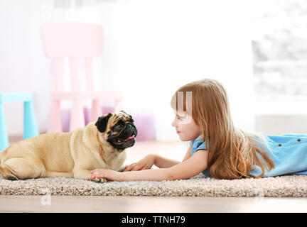 Cute girl playing with dog on carpet - Stock Photo