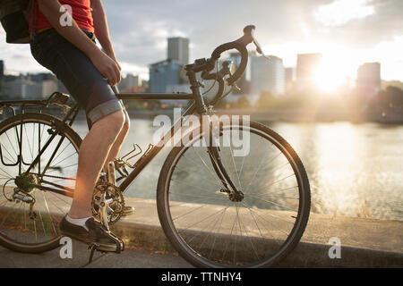 Low section of man riding bicycle on street by lake during sunset - Stock Photo
