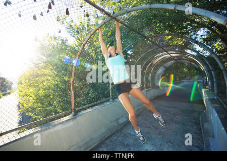 Sporty woman hanging from metallic arch over footpath at park - Stock Photo