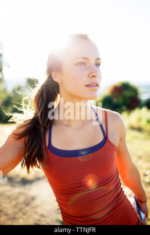 Thoughtful young woman exercising on field against clear sky during summer - Stock Photo