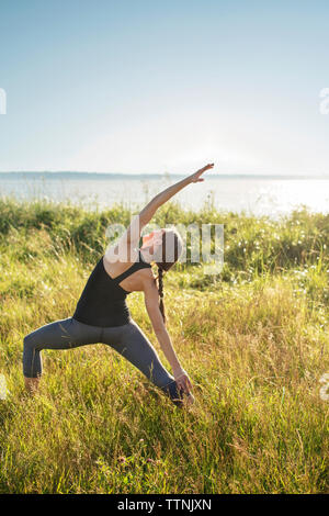 Woman practicing extended side angle pose yoga on grassy field by sea during sunny day - Stock Photo