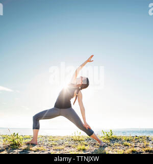 Woman practicing extended side angle pose yoga at beach during sunny day - Stock Photo