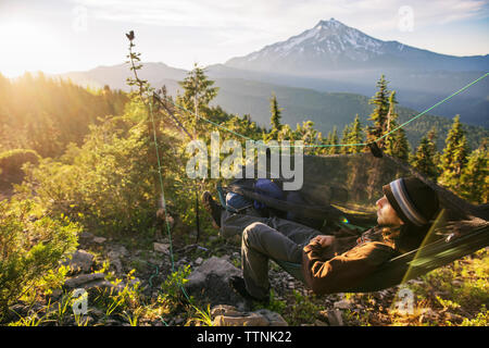 High angle view of hiker relaxing in hammock on mountain - Stock Photo