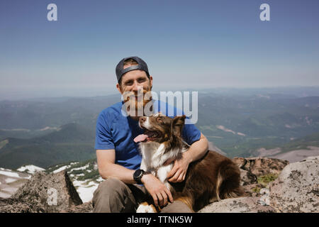 Portrait of man with dog sitting on mountain against sky - Stock Photo