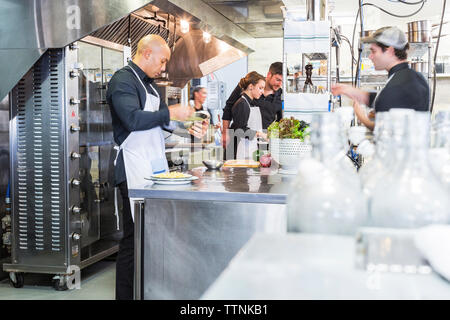 Chefs preparing food in commercial kitchen at restaurant - Stock Photo