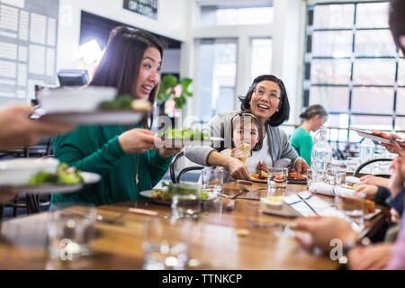 Happy family having lunch in restaurant - Stock Photo