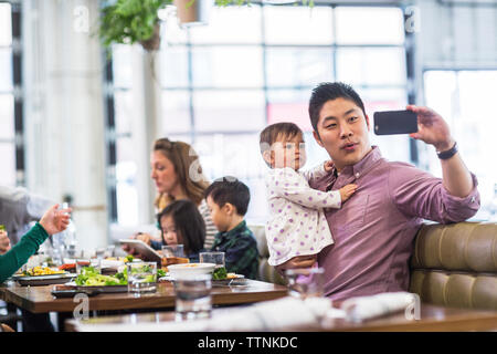Father taking selfie with baby girl while sitting with family in restaurant - Stock Photo