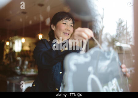 Female owner hanging open sign on window of plant shop seen through glass - Stock Photo