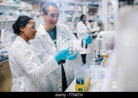 Doctors examining test tubes while coworker working in background at laboratory - Stock Photo