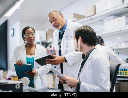 Male doctor discussing medical records with coworkers in hospital - Stock Photo