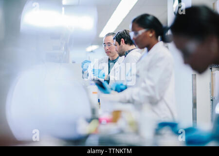 Doctors examining test tubes in laboratory - Stock Photo