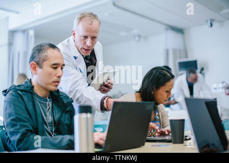 Male doctor discussing with coworkers over laptop computer in medical room