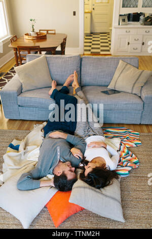High angle view of couple relaxing on carpet at home - Stock Photo