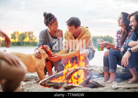 Happy friends with dog by campfire against river - Stock Photo