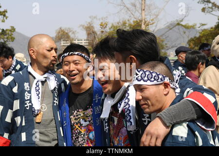 Young men celebrating and laughing after pushing floats in the Inuyama festival wearing headbands and traditional jackets - Stock Photo