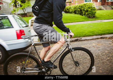 Low section of male commuter riding bicycle on street - Stock Photo