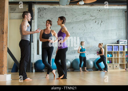 Male instructor guiding women in gym - Stock Photo