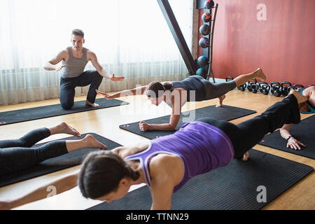 Male instructor guiding women in doing plank pose on exercise mats at gym - Stock Photo