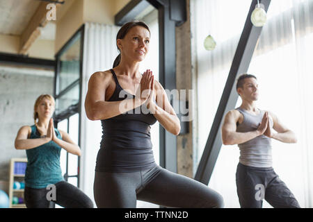 Male instructor with women practicing tree pose in gym - Stock Photo