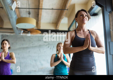 Women practicing tree pose in health club - Stock Photo